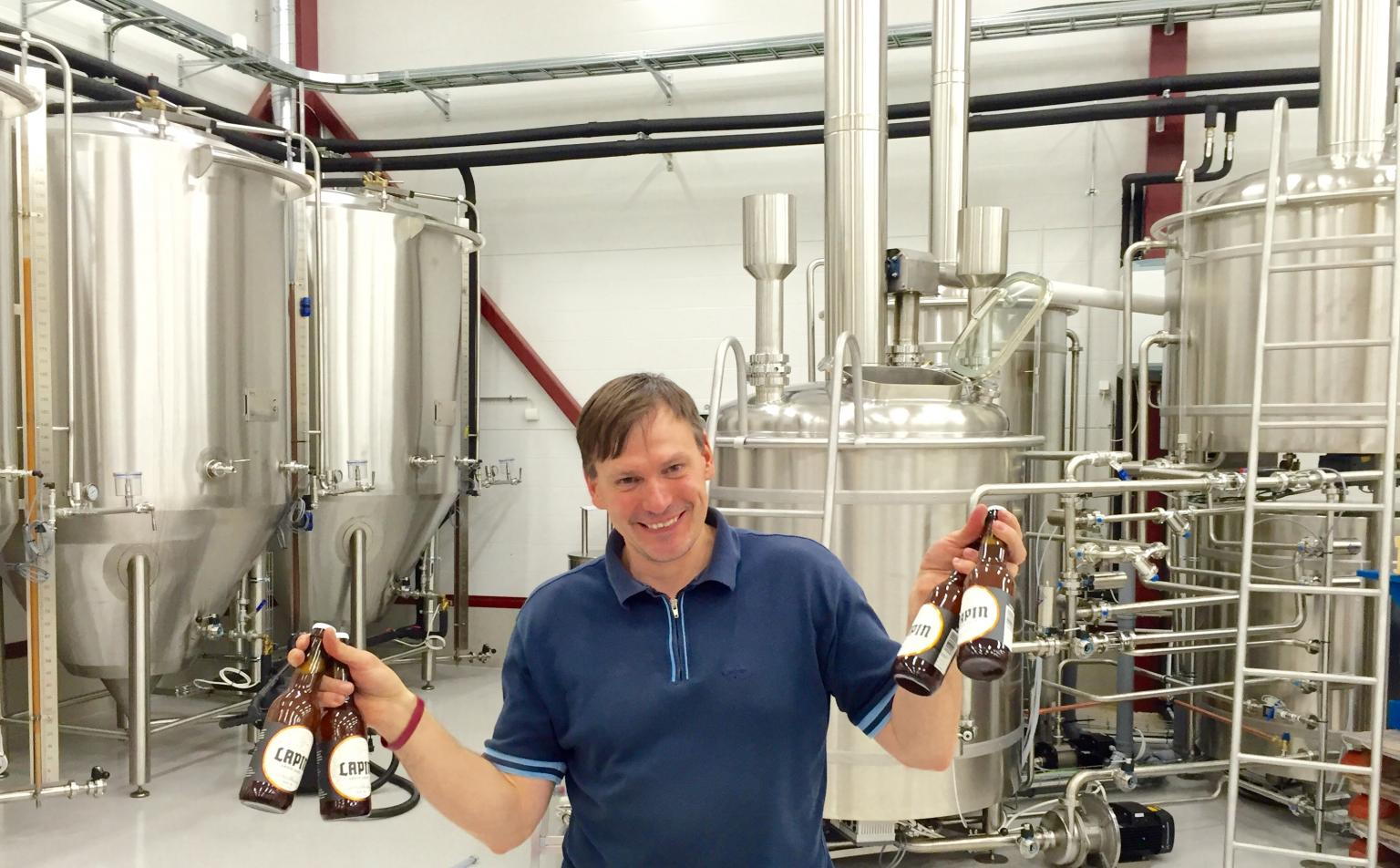 A proud brewery owner showing off the first beers produced since his factory installed its Flecks Mixer