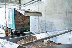 The truck unloads wood chips, fresh from the forest, onto a drag chain discharger. The unloading process takes about 15 minutes