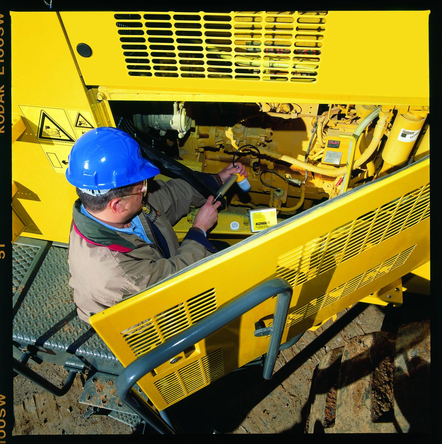 A serviceman of the Power Motive Corporation in Colorado, US, sampling oil under the Komatsu Oil and Wear Analysis (KOWA) procedure for condition monitoring. Note the easily accessible service point