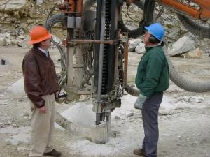 "Tom Donovan of Capitol Construction (left) with a temperature gauge and Gary Davidson (right) of Yankee. Tom Donovan confirms that, ""the temperature of the new steel's couplings averaged under 200º F. This lower temperature is due almost entirely to the greater straightness of holes drilled with the Sandvik60 steel."""